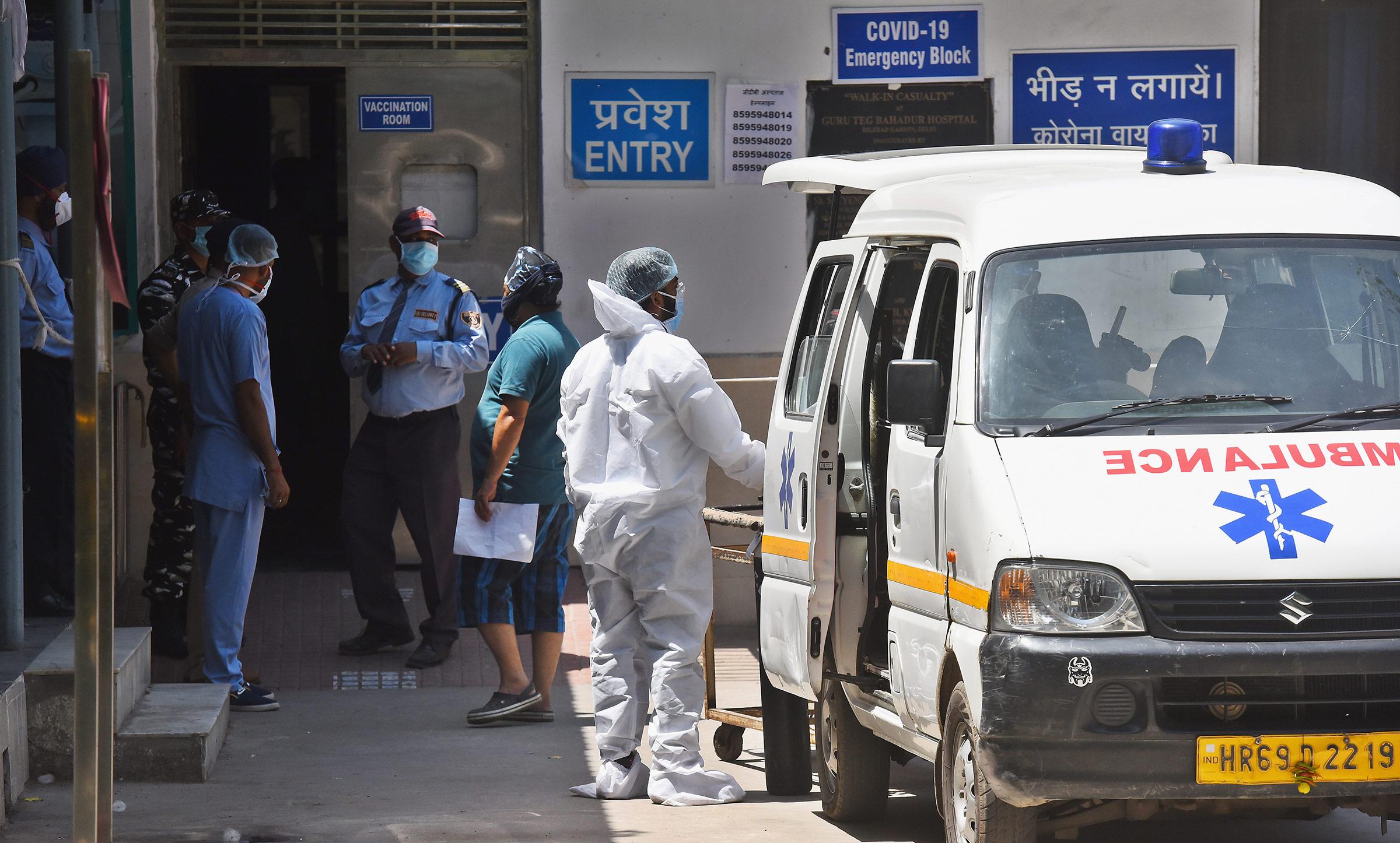 Health workers tend to a Covid-19 patient at Guru Teg Bahadur Hospital on April 25, in New Delhi, India.