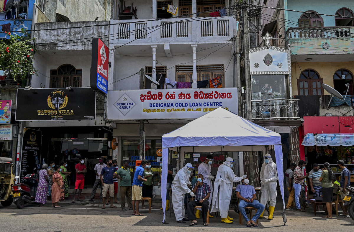 Health workers wearing protective gear collect swab samples from residents to test for Covid-19 in Colombo, Sri Lanka on May 4.