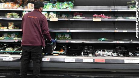 A worker restocks empty shelves inside a Sainsbury's supermarket in London on September 7, 2021